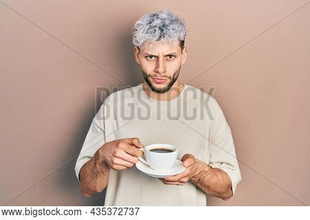 Young hispanic man with modern dyed hair drinking a cup of coffee skeptic and nervous, frowning upset because of problem. negative person.