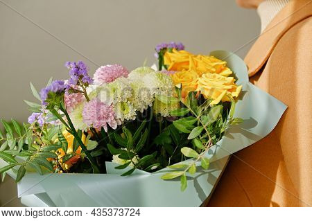 A Woman In A Beige Coat Holds A Beautiful Autumn Bouquet In Her Hands. Depersonalization Concept. Cl
