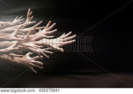 A Lot Of Hands Aggressively Reaching Forward. Black Background. Copy Space. The Concept Of Bullying,