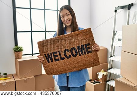 Young chinese girl smiling happy holding welcome doormat at new home
