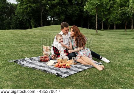 Young Family On A Picnic In The Park At Sunset. The Picnic Basket Lies On The Bedspread. Happy Famil