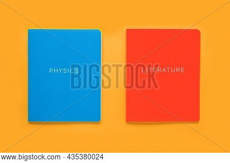 Multicolored Exercise Books Over The Orange Background, Close Up. Education And Reading Concept - Gr