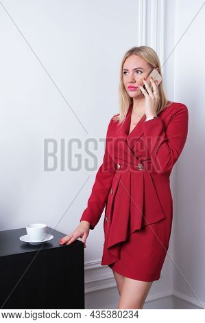 Vertical Portrait Of A Young Attractive Woman In A Red Business Dress With A Phone In Her Hands. A B