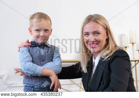 A Young Smiling Woman Blonde In A Black Blazer And A Little Boy Portraying A Businessman. Mom Is A B