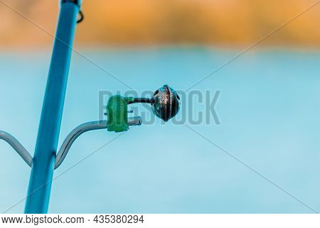 A Fishing Bell For A Fishing Rod Close-up On The Background Of A Quiet River On A Sunny Day. Fishing