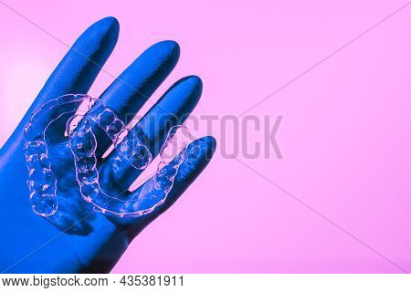 A Hand In A Blue Glove Holds Aligners For Aligning Teeth On A Pink Background. Plastic Braces Dentis
