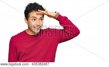 Young handsome man wearing casual clothes very happy and smiling looking far away with hand over head. searching concept.