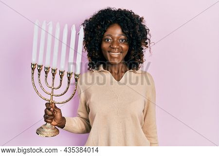 Young african american woman holding menorah hanukkah jewish candle looking positive and happy standing and smiling with a confident smile showing teeth