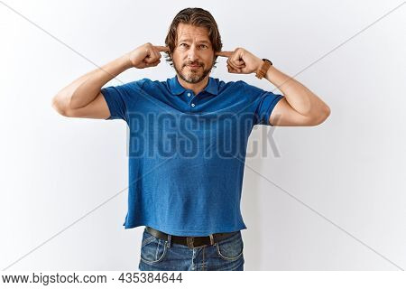 Handsome middle age man standing together over isolated background covering ears with fingers with annoyed expression for the noise of loud music. deaf concept.