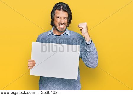 Middle age handsome man holding blank empty banner annoyed and frustrated shouting with anger, yelling crazy with anger and hand raised