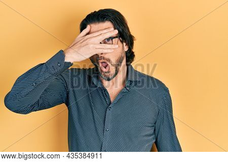 Middle age caucasian man wearing casual clothes and glasses peeking in shock covering face and eyes with hand, looking through fingers afraid