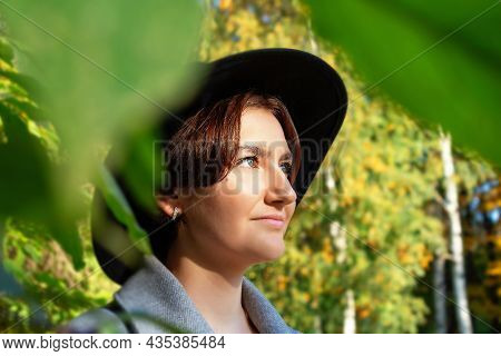 Young Caucasian Woman In Black Hat With Wide Brim And Grey Coat. Tourist In Autumn Park.