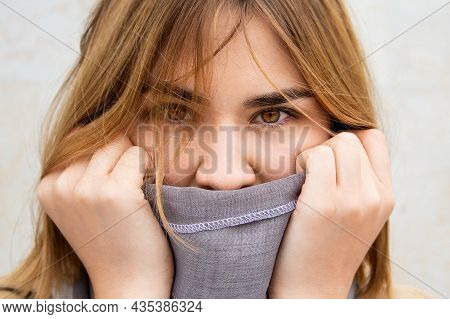Close-up Portrait Caucasian Woman Wrapped In Grey Scarf. Young Woman With Amazing Brown Eyes.