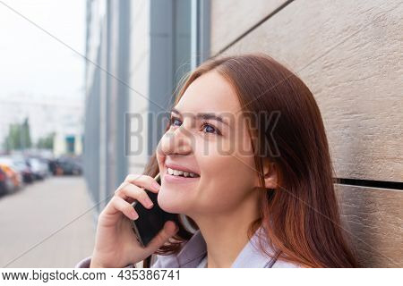 Attractive Beautiful Caucasian Girl - Student Calling Somebody And Smiling. Girl Is Standing On Stre