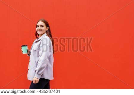 Beautiful Young Caucasian Woman In Casual Clothing Walking And Holding Glass Of Coffee Red Wall. Loo