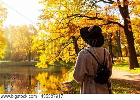 Unrecognizable Woman In Grey Coat, Black Hat With Wide Brim And Small Black Backpack In Autumn Park,