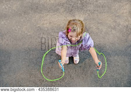 Little Preschool Girl Jump And Train With Skipping Rope. View From Above On Cute Happy Active Child.