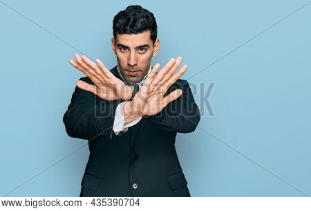 Handsome hispanic man wearing business clothes rejection expression crossing arms and palms doing negative sign, angry face