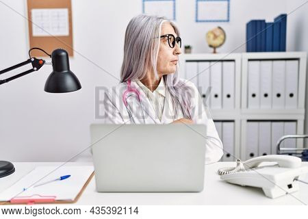 Middle age grey-haired woman wearing doctor uniform working using computer laptop looking to side, relax profile pose with natural face with confident smile.