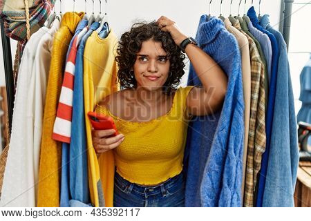 Young hispanic woman searching clothes on clothing rack using smartphone confuse and wondering about question. uncertain with doubt, thinking with hand on head. pensive concept.