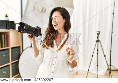 Beautiful caucasian woman working as photographer at photography studio winking looking at the camera with sexy expression, cheerful and happy face.