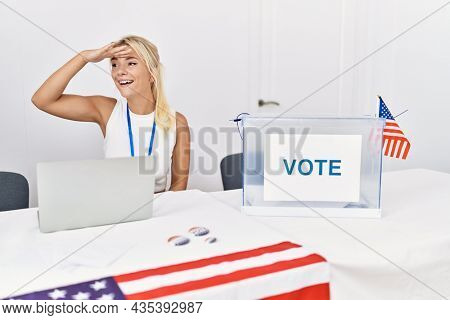 Young caucasian woman at america political campaign election very happy and smiling looking far away with hand over head. searching concept.