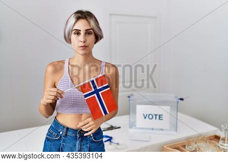 Young beautiful woman at political campaign election holding norway flag thinking attitude and sober expression looking self confident