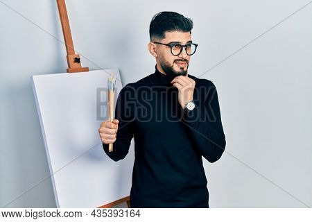 Handsome man with beard holding brushes close to easel stand thinking worried about a question, concerned and nervous with hand on chin