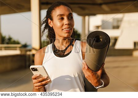 Black sportswoman using mobile phone while standing with fitness mat on parking outdoors