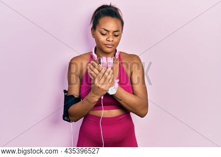 Young african american girl wearing gym clothes and using headphones suffering pain on hands and fingers, arthritis inflammation