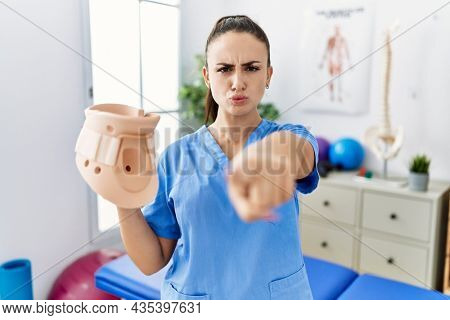 Young physiotherapist woman holding cervical neck collar at medical clinic pointing with finger to the camera and to you, confident gesture looking serious