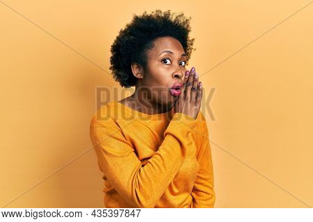 Young african american woman wearing casual clothes hand on mouth telling secret rumor, whispering malicious talk conversation