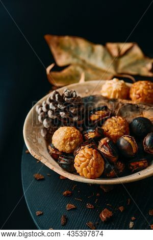a plate with food traditionally eaten in All Saints Day in Catalonia, Spain, in a party called Castanada, such as roasted chestnuts, roasted sweet potato and panellets, a confection made with marzipan