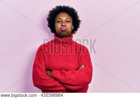 Young african american woman with arms crossed gesture puffing cheeks with funny face. mouth inflated with air, catching air.