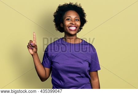 African american woman with afro hair wearing casual purple t shirt pointing finger up with successful idea. exited and happy. number one.