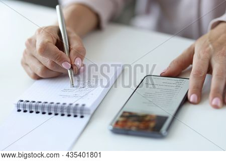 Woman Is Rewriting Prescription From Smartphone Into Notebook