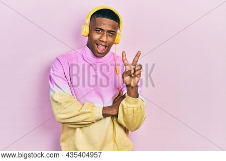 Young black man listening to music wearing headphones smiling with happy face winking at the camera doing victory sign. number two.
