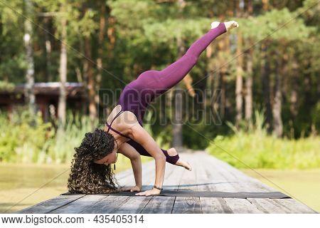 A Woman Practicing Yoga, Performs The Eka Pada Bakasana Exercise, Crane Pose, Stands On A Wooden Bri