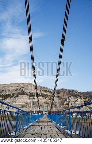 A New And Sturdy Wooden Suspension Bridge Over A Wide River Goes To The Mountain. A Shot With A Magn