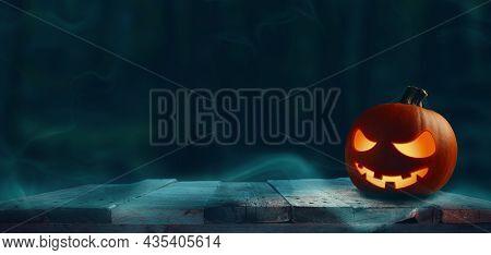 Carved Halloween Pumpkin Jack O Lantern On A Rustic Wooden Plank, Happy Halloween, Dark Forest