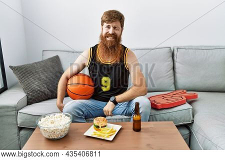 Caucasian man with long beard holding basketball ball cheering tv game winking looking at the camera with sexy expression, cheerful and happy face.