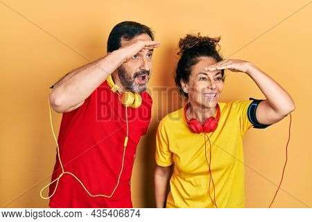 Middle age couple of hispanic woman and man wearing sportswear and arm band very happy and smiling looking far away with hand over head. searching concept.