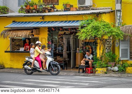 Traditional Vietnamese Cafe With A Roadside Terrace, Decorated With Flowers. Visitors Spend Time In