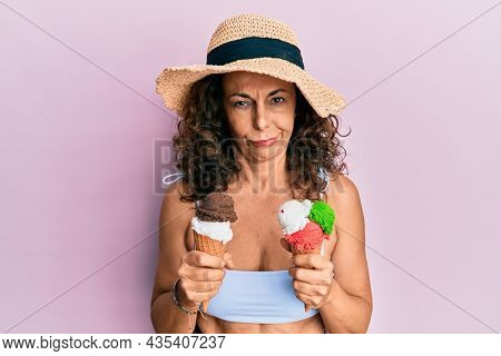Middle age hispanic woman wearing summer style holding ice cream skeptic and nervous, frowning upset because of problem. negative person.
