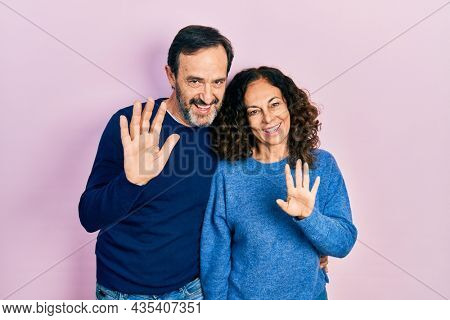 Middle age couple of hispanic woman and man hugging and standing together waiving saying hello happy and smiling, friendly welcome gesture