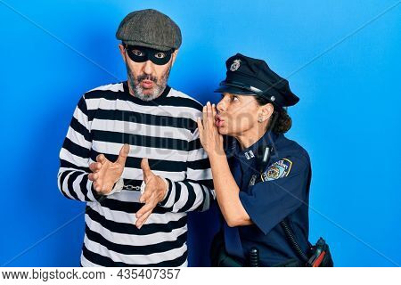 Middle age couple of hispanic woman and man wearing thief and police uniform hand on mouth telling secret rumor, whispering malicious talk conversation