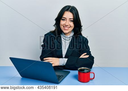 Beautiful hispanic business woman with arms crossed gesture at the office smiling with a happy and cool smile on face. showing teeth.