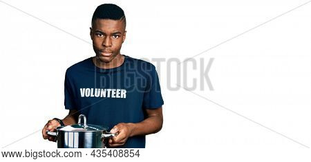 Young african american man wearing volunteer holding cooking pot skeptic and nervous, frowning upset because of problem. negative person.