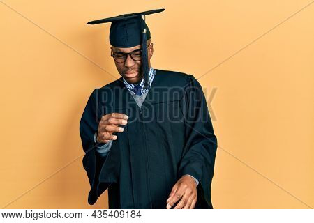 Young african american man wearing graduation cap and ceremony robe disgusted expression, displeased and fearful doing disgust face because aversion reaction.