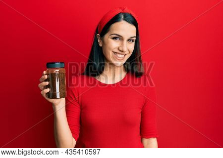 Young hispanic woman holding soluble coffee looking positive and happy standing and smiling with a confident smile showing teeth